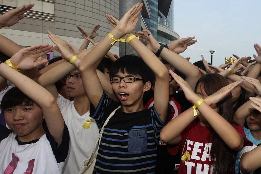 Scholarism founder Joshua Wong (centre) and other members chant slogans during a flag raising ceremony in Hong Kong on Oct 1, 2014. -- PHOTO: REUTERS