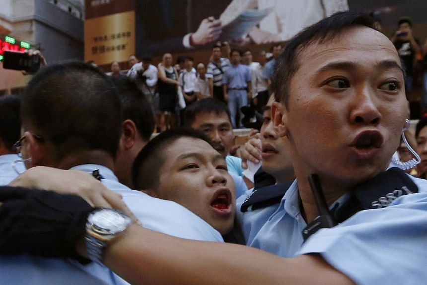 A pro-democracy protester (centre) bleeds in the month as he is escorted by the police after being beaten by anti-Occupy Central protesters at Hong Kong's shopping Mongkok district, where a main road is occupied, on Oct 3, 2014. -- PHOTO: REUTERS