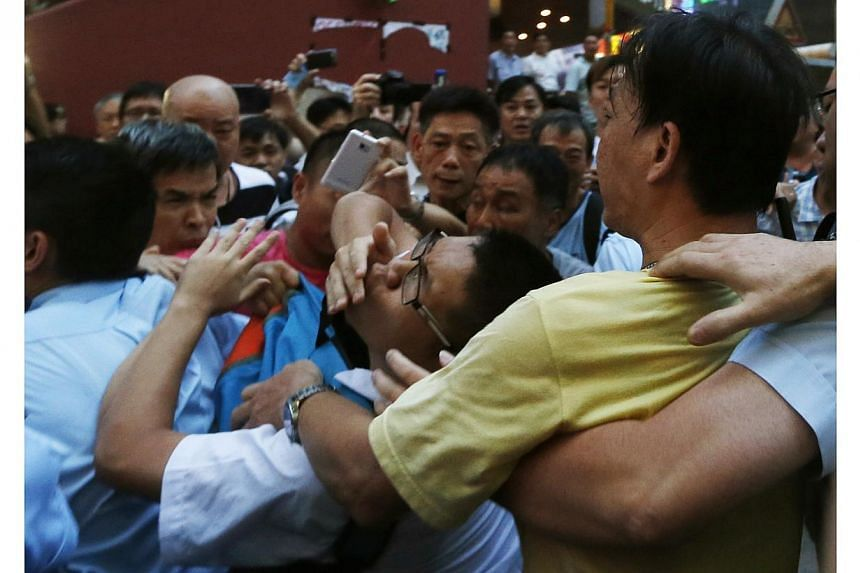 A pro-democracy protester (centre) is grabbed by an anti-Occupy Central protester (R) at Hong Kong's shopping Mongkok district, where a main road is occupied, on Oct 3, 2014. -- PHOTO: REUTERS