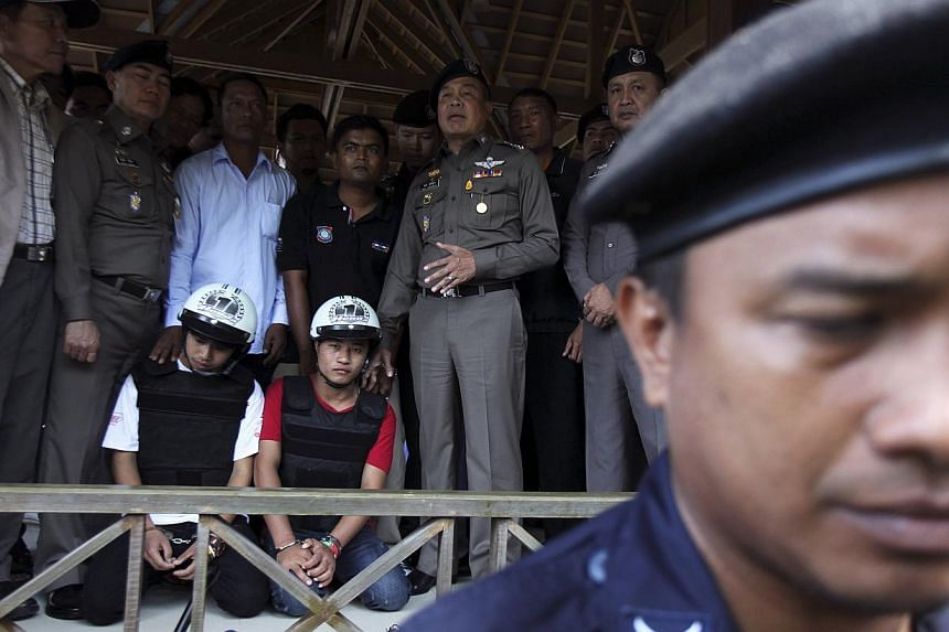 Thai national police chief Police General Somyot Poompanmoung (centre) stands next to two detained workers from Myanmar, suspected of killing two British tourists on the island of Koh Tao last month, on Oct 3, 2014.Two Myanmar workers have conf