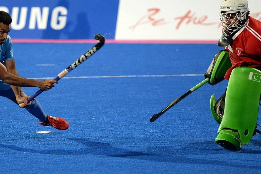 Indian player Dharamvir Singh (left) scores the final goal in the penalty shoot-out of the men's hockey final against Pakistan. It was a chance for both countries - who were once giants in the game - to recapture past glory and spark off a revival of