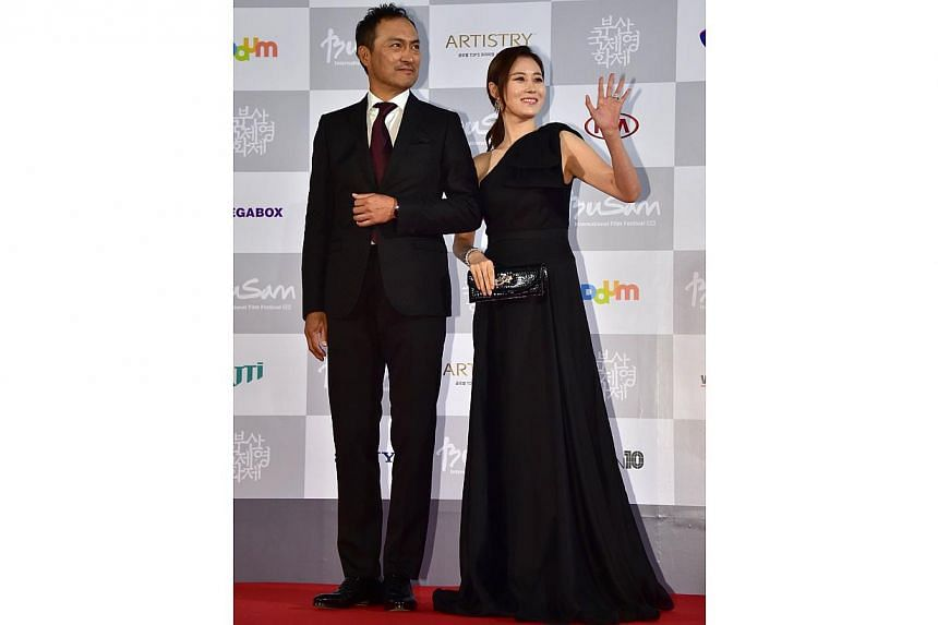 South Korean actress Moon So Ri (right) and Japanese actor Ken Watanabe (left) pose on the red carpet for the opening ceremony of the 19th Busan International Film Festival (BIFF) at the Busan Cinema Center in Busan on Oct 2, 2014. -- PHOTO: AFP&nbsp