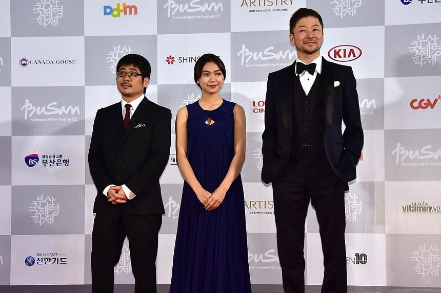(Left-right) Japanese director Kazuyoshi Kumakiri, actress Fumi Nikaido and actor Tadanobu Asano pose on the red carpet for the opening ceremony of the 19th Busan International Film Festival (BIFF) at the Busan Cinema Center in Busan on Oct 2, 2014.