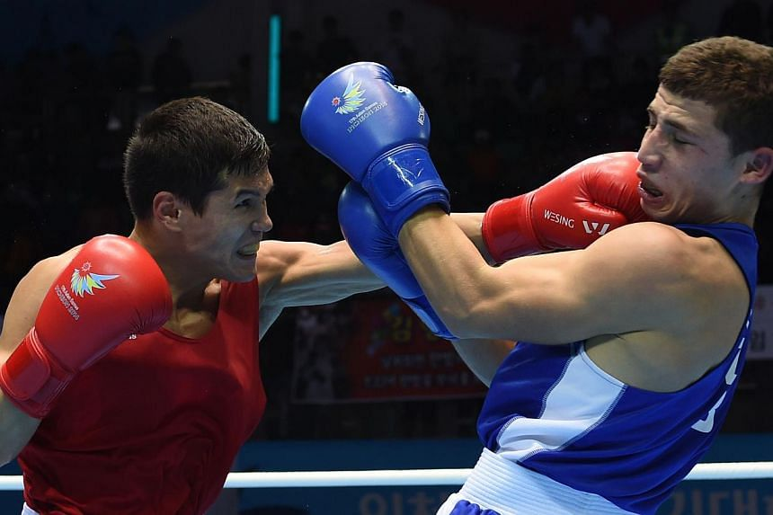 Kazakhstan's Daniyar Yeleussinov (left) lands a left on Uzbekistan's Israil Madrimov (right) in the men's welterweight (69kg) final boxing match during the 17th Asian Games at the Seonhak Gymnasium in Incheon on Oct 3, 2014. -- PHOTO: AFP