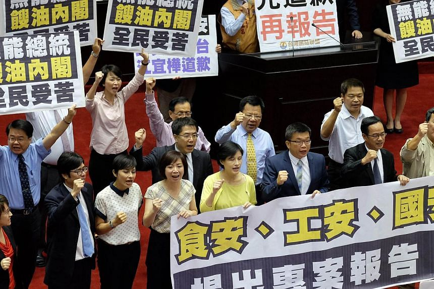 Opposition lawmakers from the Democratic Progressive Party (DPP) and Taiwan Solidarity Union (TSU) display placards demanding Premier Jiang Yih-hua (not in picture) apologise for the gutter oil scandal before his speech during the new session at the