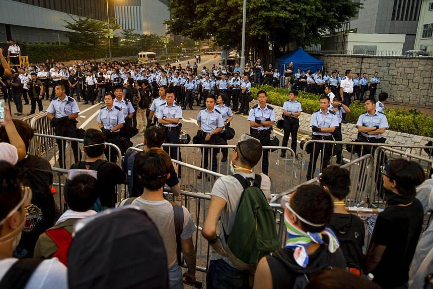 Police line up next to government offices in Hong Kong on Oct 3, 2014. -- PHOTO: AFP