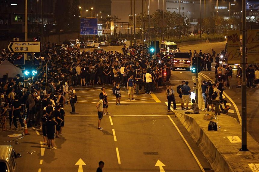Protesters block a section of an avenue in front of the office of Hong Kong's Chief Executive Leung Chun-ying in Hong Kong, on Oct 3, 2014. -- PHOTO: REUTERS