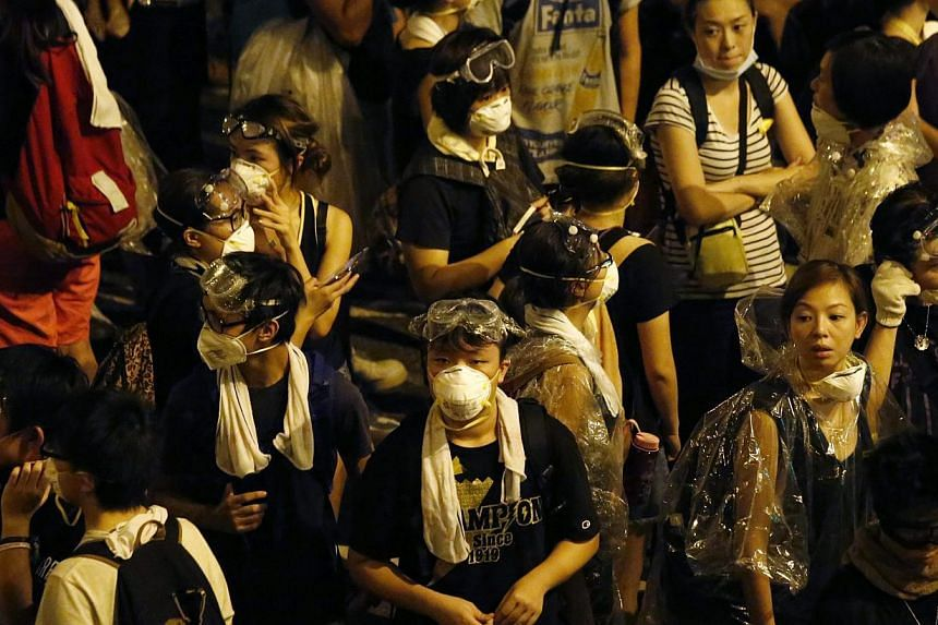 Pro-democracy protesters wearing protective gear for a possible confrontation with the police gather outside the chief executive office in Hong Kong late on Oct 2, 2014. -- PHOTO: REUTERS