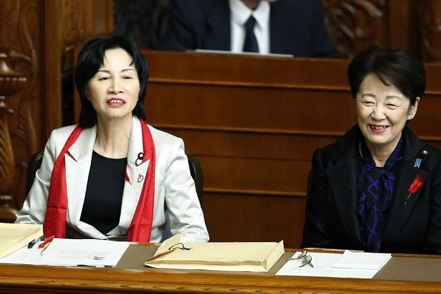 Japan's Justice Minister Midori Matsushima (left) attending the Upper House plenary session at the parliament in Tokyo on Oct 1, 2014, with the red scarf, which caused a dress code row. -- PHOTO: AFP
