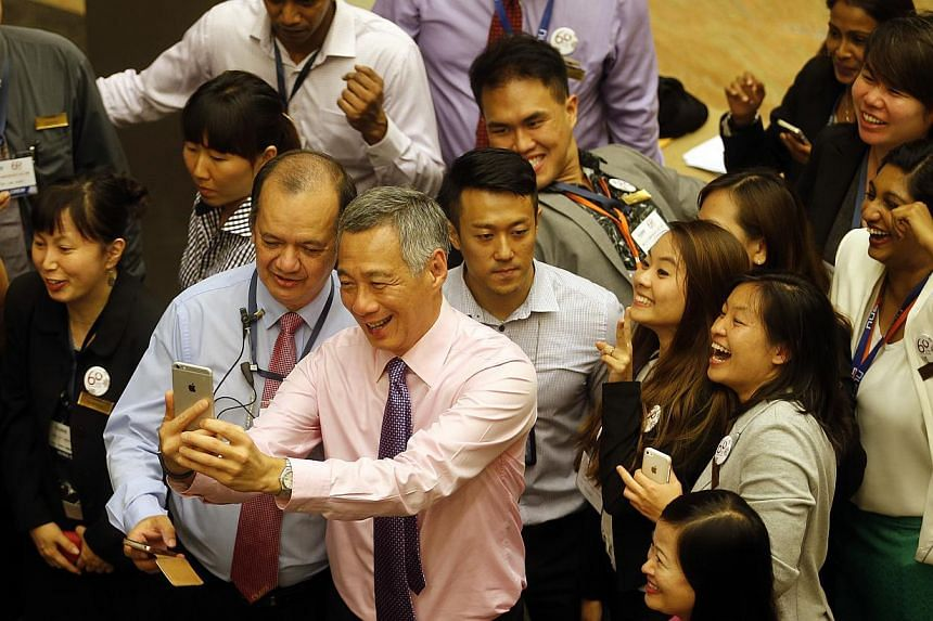 Prime Minister Lee Hsien Loong taking a selfie with members of the audience after giving a speech at the National University of Singapore Society.-- ST PHOTO:CHEW SENG KIM