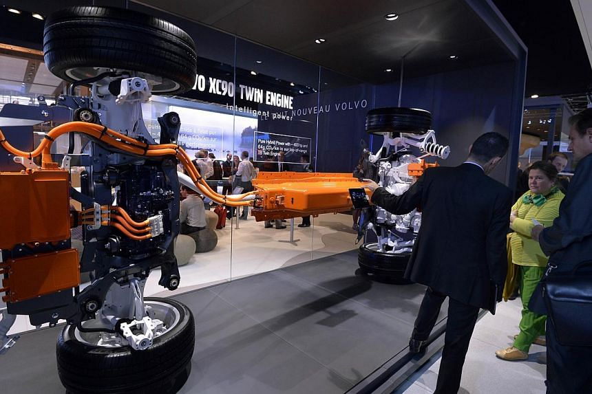 Journalists look at the engine of the new Volvo XC90 at the 2014 Paris Auto Show on Oct 2, 2014 in Paris, on the first of the two press days. -- PHOTO: AFP