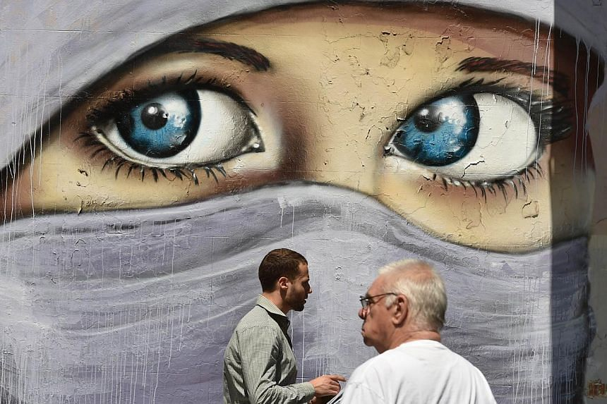 People walk past a mural of a Muslim woman painted on a wall in an inner city suburb in Sydney on Oct 2, 2014. Australian Prime Minister Tony Abbott asked officials to re-think restrictions on members of the public wearing face-coverings such as burq