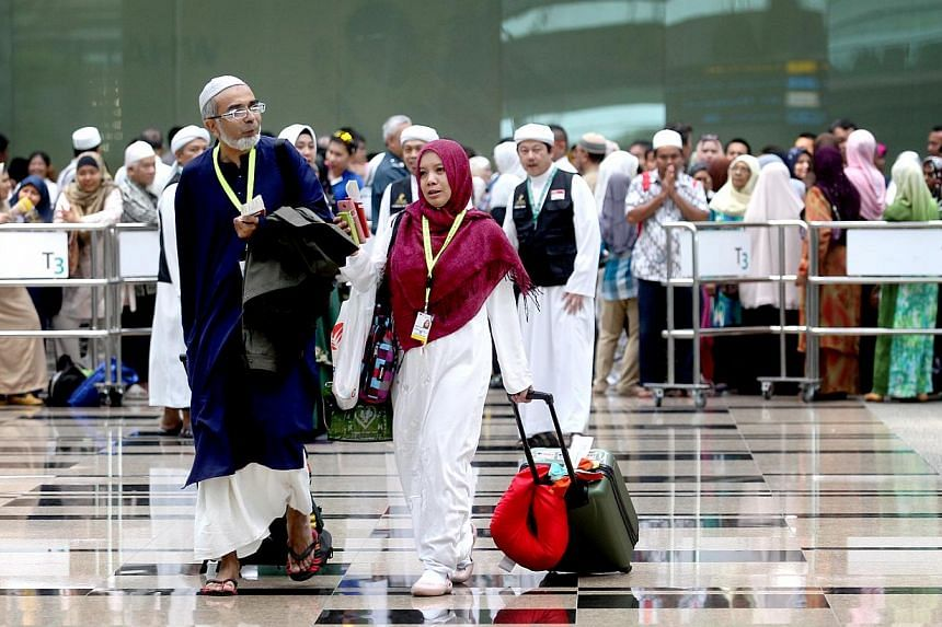 Family members and friends gathered at Changi Airport's Terminal 3 on Oct 3, 2013, for an emotional farewell to their loved ones going for their haj. -- ST PHOTO: CHEW SENG KIM