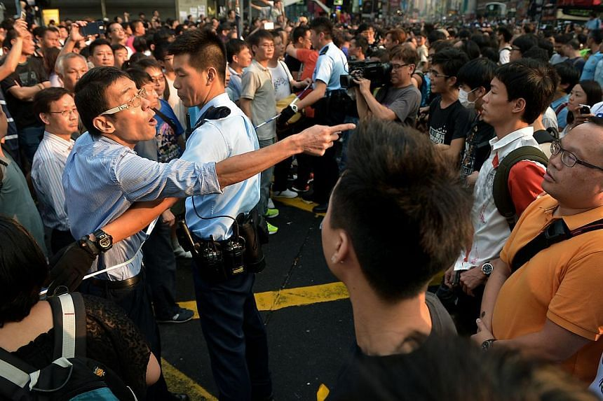 An anti-occupy demonstrator (left) shouts at pro-occupy demonstrators (right) during an altercation in Mongkok late on Friday, Oct 3, 2014.It is the responsibility of Hong Kong and Beijing to make one country, two systems work, and if other par