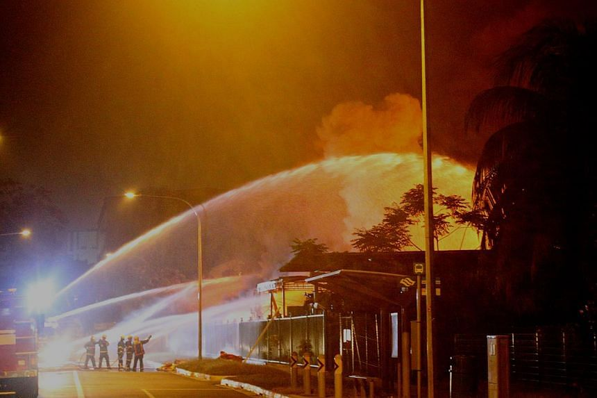 Firefighters encircling the fire with water jets. -- PHOTO: SCDF