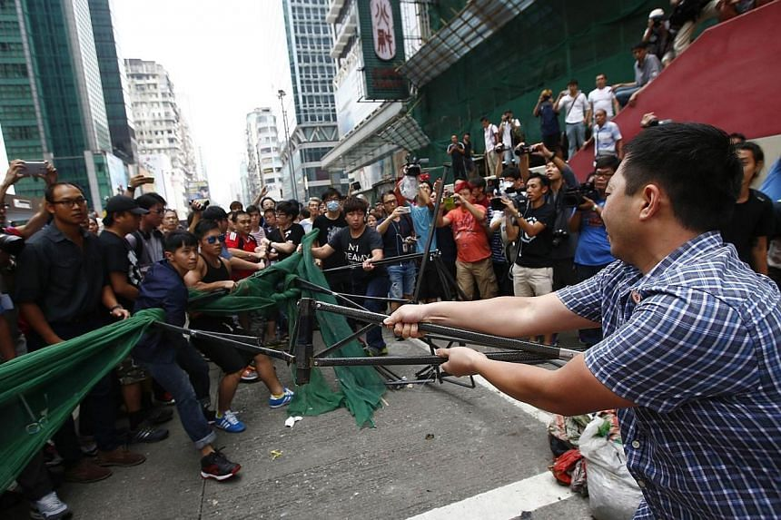 Anti-Occupy Central protesters (right) try to remove a barricade from pro-democracy protesters at a main street at Hong Kong's Mongkok shopping district on Oct 4, 2014. -- PHOTO: REUTERS