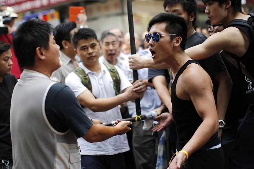 Locals look on as anti-Occupy Central protesters argue with pro-democracy protesters at a main street at Hong Kong's Mongkok shopping district on Oct 4, 2014. -- PHOTO: REUTERS