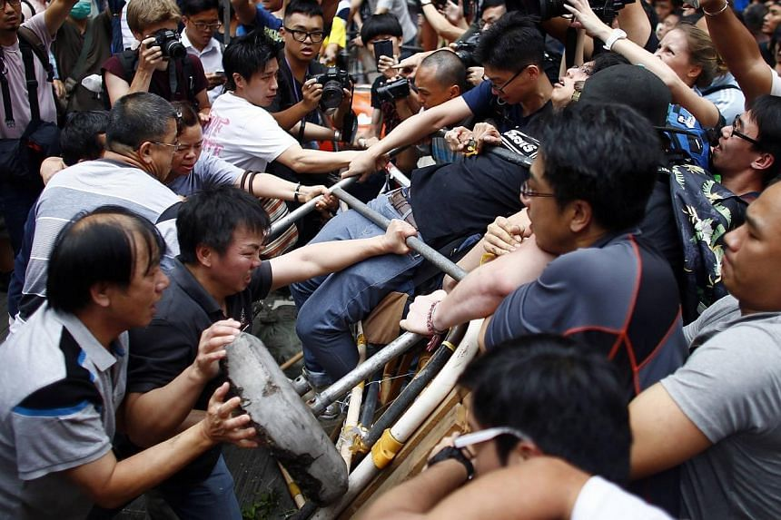 Anti-Occupy Central protesters (left) try to remove a barricade from pro-democracy protesters on a main street in Hong Kong's Mongkok shopping district on Oct 4, 2014. -- PHOTO: REUTERS
