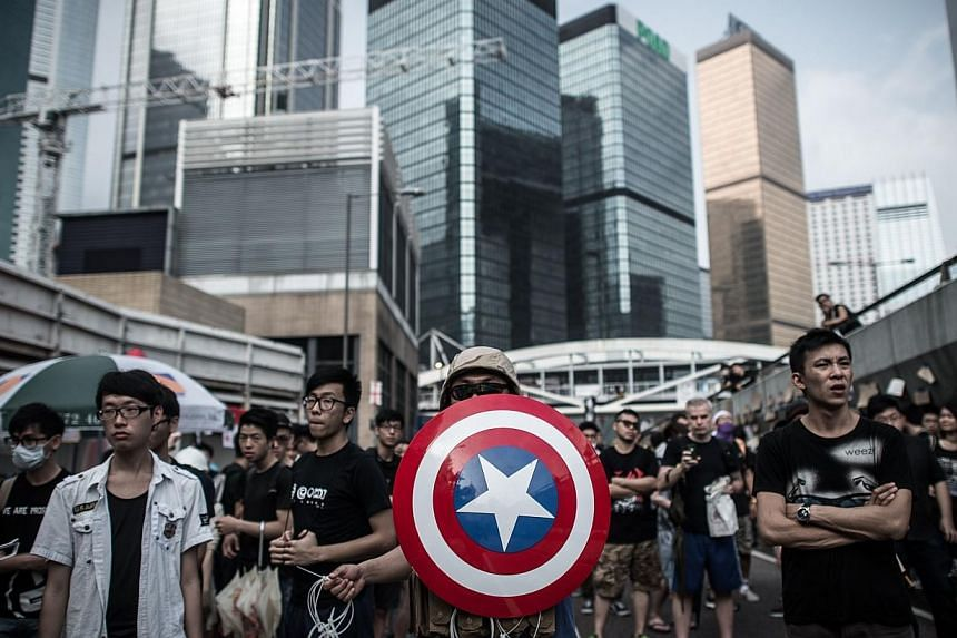 Pro-democracy protesters, including one carrying a shield from the Captain America comic book series stand their ground as they look out for the presence of rival protest groups next to a barricade on a road in Hong Kong on Oct 4, 2014. -- PHOTO: REU
