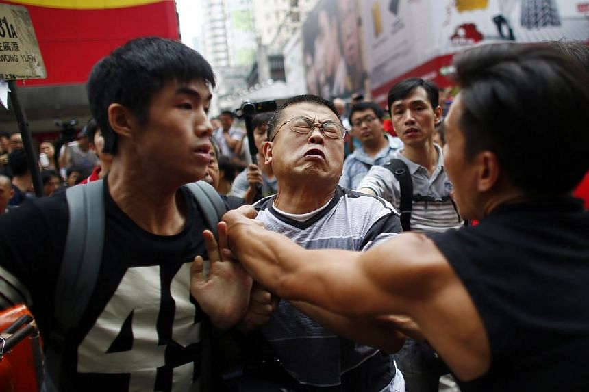 An anti-Occupy Central protester (centre) scuffles with pro-democracy protesters as he tries to remove a barricade at a main street at Hong Kong's Mongkok shopping district on Oct 4, 2014. -- PHOTO: REUTERS