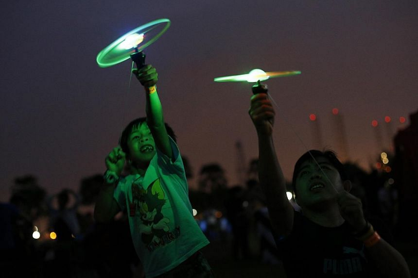 Cheow Jun Wei plays with a LED flying disc alongside his father, Cheow Yoon Foo. -- PHOTO: DESMOND LUI FOR THE STRAITS TIMES