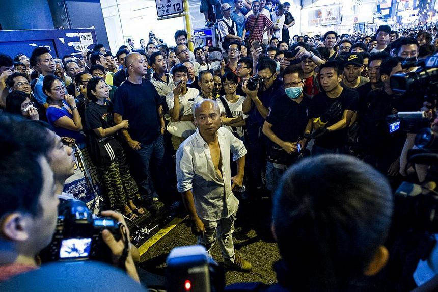 A pro-government protester is surrounded by Pro democracy protester during clashes between rival protest groups in Hong Kong, on Oct 3, 2014. -- PHOTO: AFP