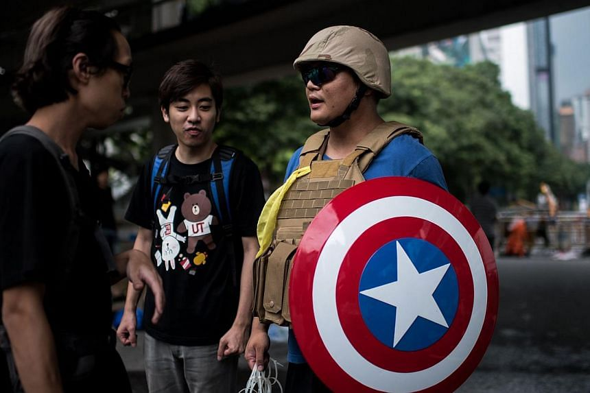 Pro-democracy protesters talk to a man carrying a shield, from the Captain America comic book series, and plastic wires to restrain people, next to a barricade on a road in Hong Kong, on Oct 4, 2014. -- PHOTO: AFP