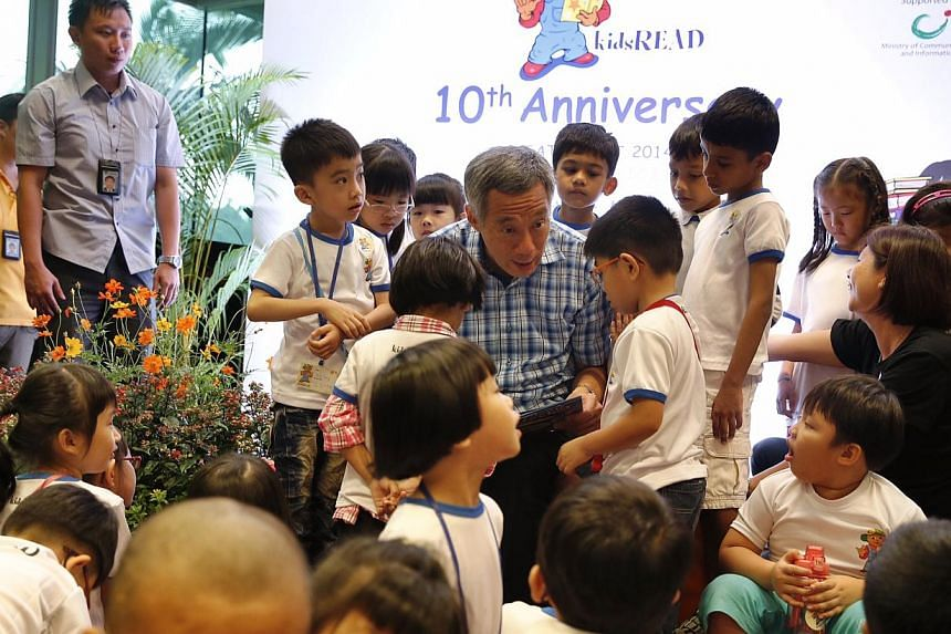 Prime Minister Lee Hsien Loong reads a story book titled Go To Sleep, Gecko! to kids during National Library Board's 10th year celebration of kidsREAD at Ang Mo Kio Public Library on Oct 4, 2014. -- ST PHOTO: KEVIN LIM