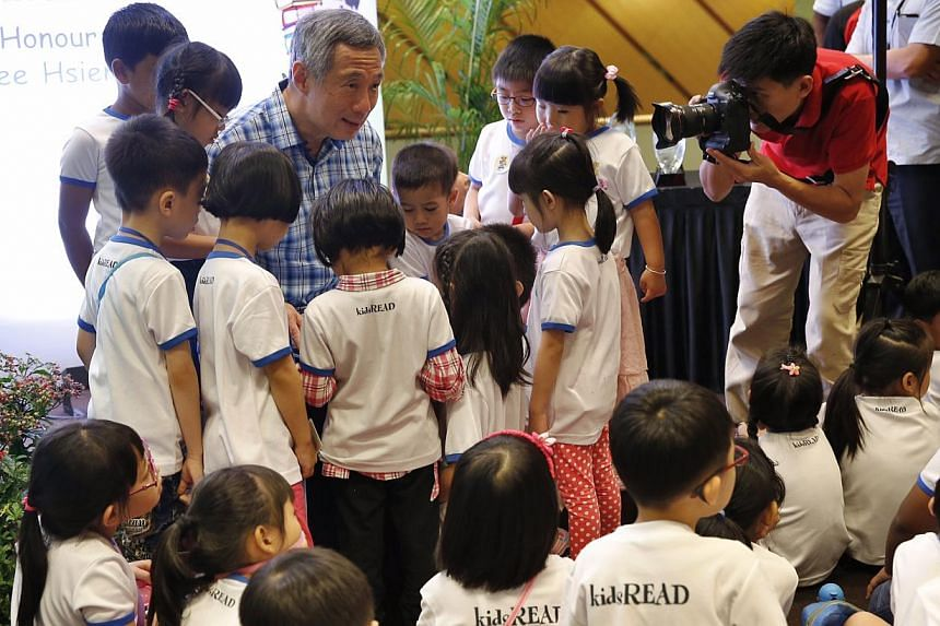 Prime Minister Lee Hsien Loong is surrounded by kids as he reads a story book titled Go To Sleep, Gecko! to them during National Library Board's 10th year celebration of kidsREAD at Ang Mo Kio Public Library on Oct 4, 2014. -- ST PHOTO: KEVIN LIM