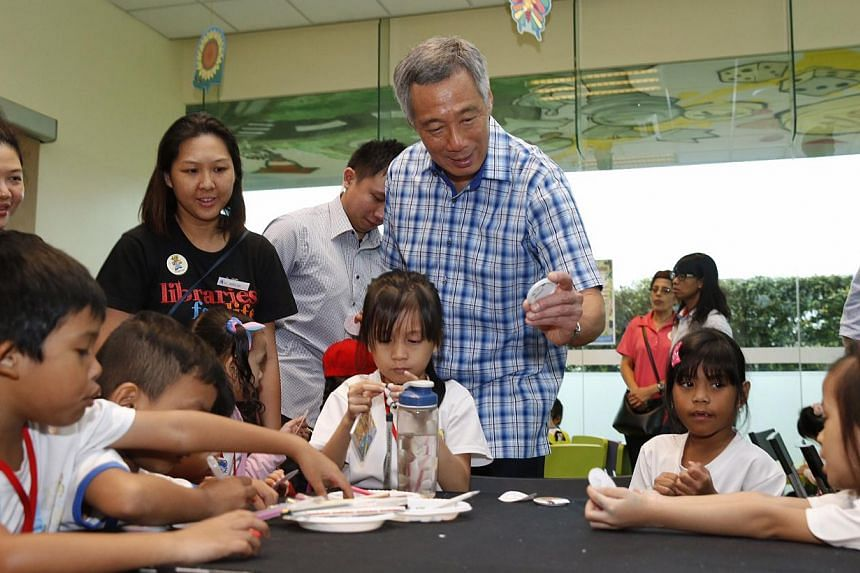 Prime Minister Lee Hsien Loong looks at badge-making by kids during National Library Board's 10th year celebration of kidsREAD at Ang Mo Kio Public Library on Oct 4, 2014. -- ST PHOTO: KEVIN LIM