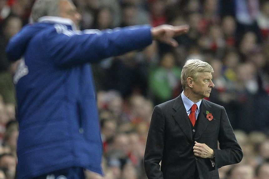 Arsenal's manager Arsene Wenger (right) watches as Chelsea's manager Jose Mourinho points during their English League Cup fourth round soccer match at Emirates Stadium in London on Oct 29, 2013. -- PHOTO: REUTERS