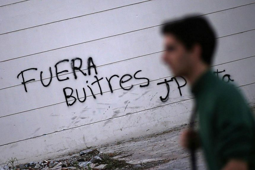 """A man passes by grafitti that reads """"Vultures, get out"""" in Buenos Aires on Sept 24, 2014. Argentine President Cristina Fernandez characterises hedge funds suing the country for full repayment of defaulted debt as """"vultures"""" out to wreck Argentina's f"""