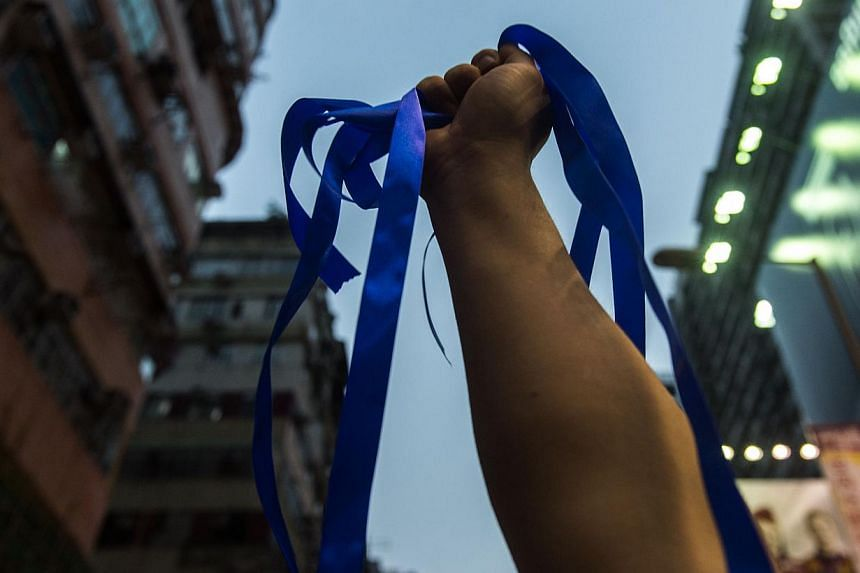 A pro-Beijing activist holds up blue ribbons for anti-Occupy Central protestors to collect as pro-Hong Kong government speeches are made in the Kowloon district of Hong Kong on Oct 4, 2014.Pro-democracy groups in Hong Kong have made yellow ribb