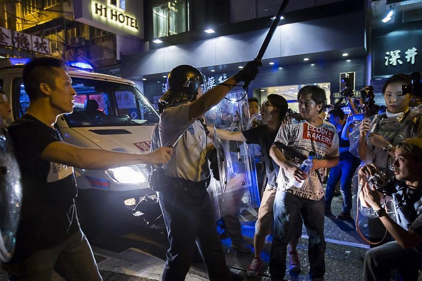 A riot police officer holds a baton as he confronts Occupy Central protesters, where a main road is occupied at Hong Kong's Mongkok district on Oct 4, 2014. -- PHOTO: AFP