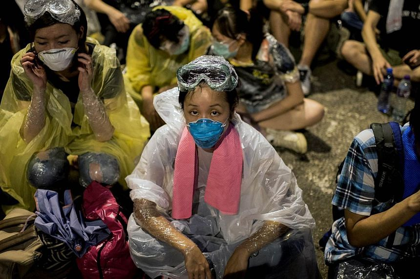 A woman wearing protective gear in anticipation of police action sits outside the central government complex on a blockaded road in Hong Kong on Oct 2, 2014. -- PHOTO: AFP
