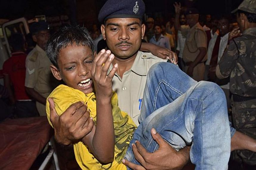 A boy who was injured in a stampede is carried to a hospital for treatment in the eastern Indian city of Patna Oct 3, 2014. At least 32 people were killed in a stampede during a Hindu festival in the eastern Indian state of Bihar on Friday, the state