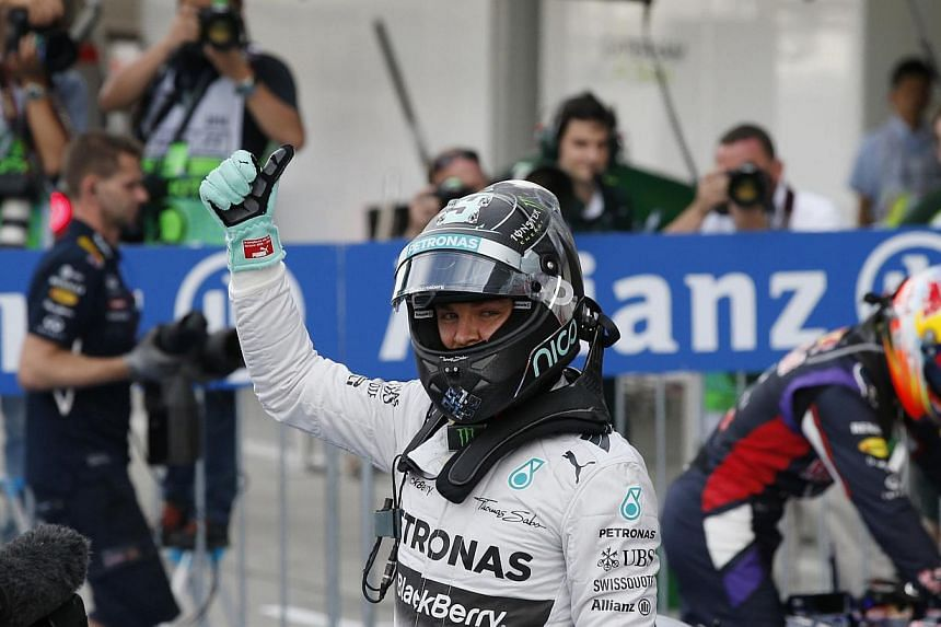 Mercedes Formula One driver Nico Rosberg of Germany gives a thumbs up as he celebrates winning pole position in the qualifying session of the Japanese F1 Grand Prix at the Suzuka Circuit on Oct 4, 2014. -- PHOTO: REUTERS