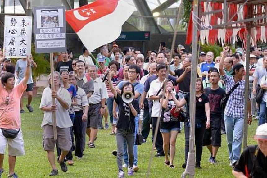 Activists Han Hui Hui (with loudspeaker) and Roy Ngerng (carrying state flag) with supporters at the Return Our CPF rally, marching round Hong Lim Park on Sept 27, 2014. -- ST PHOTO: LIM SIN THAI