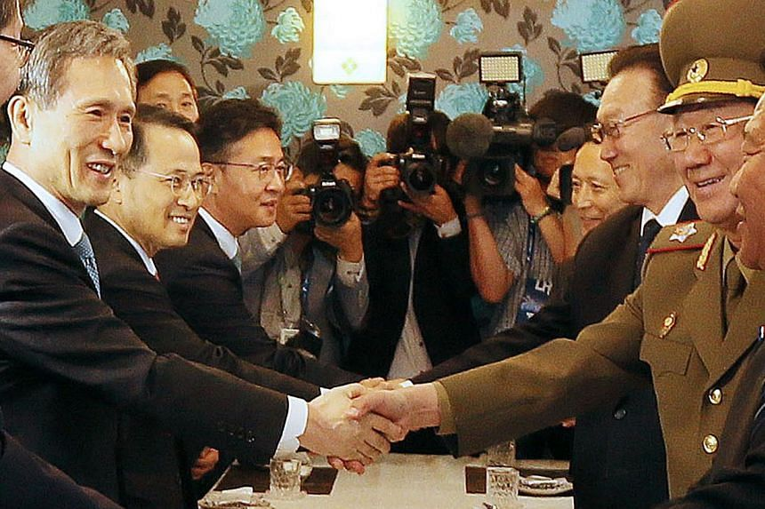 South Korea's national security advisor Kim Kwan Jin (left) shakes hands with North Korea'sGeneral Political Bureau directorHwang Pyong So (second from right) during a luncheon meeting in Incheon, west of Seoul, on Oct 4, 2014. -- PHOTO: