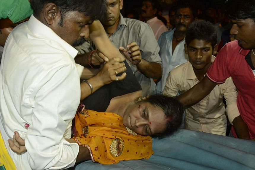 An injured woman is lifted onto a stretcher following a stampede as people celebrated the Dussehra festival, in Patna, in Bihar state, on Oct 3, 2014. A stampede at the popular religious festival in eastern India left 32 people dead and several dozen