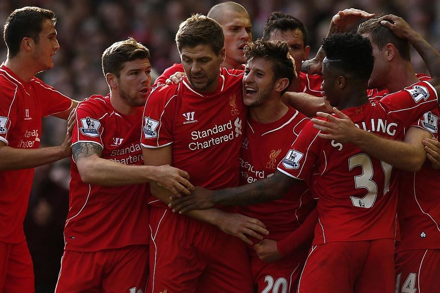 Liverpool celebrate their opening goal against Aston Villa at Anfield on Oct 4, 2014.-- PHOTO: REUTERS