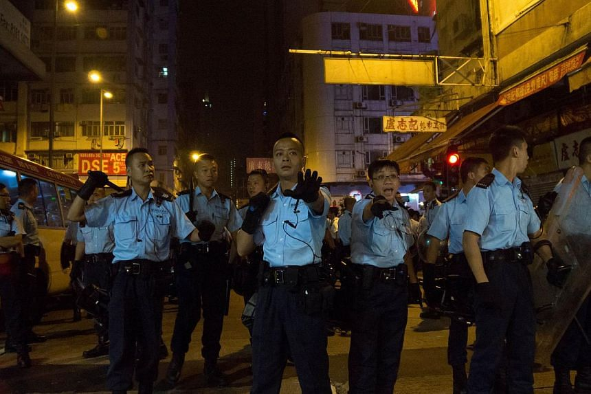 Police officers gesture at a cordon in Mongkok on Oct 5, 2014. -- PHOTO: AFP