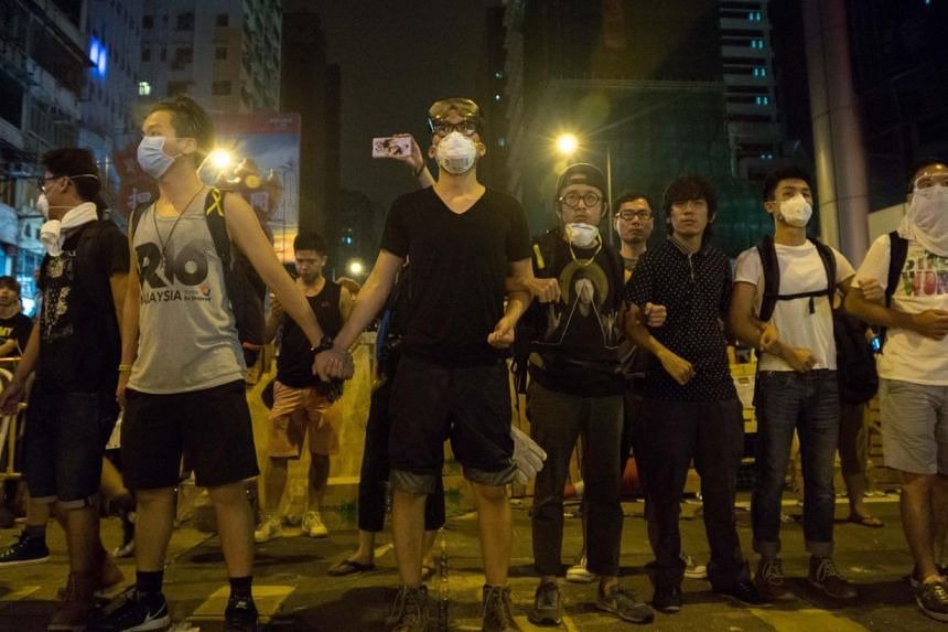 Pro-democracy demonstrators link arms and guard their protest camp in Mongkok on Oct 5, 2014. -- PHOTO: AFP