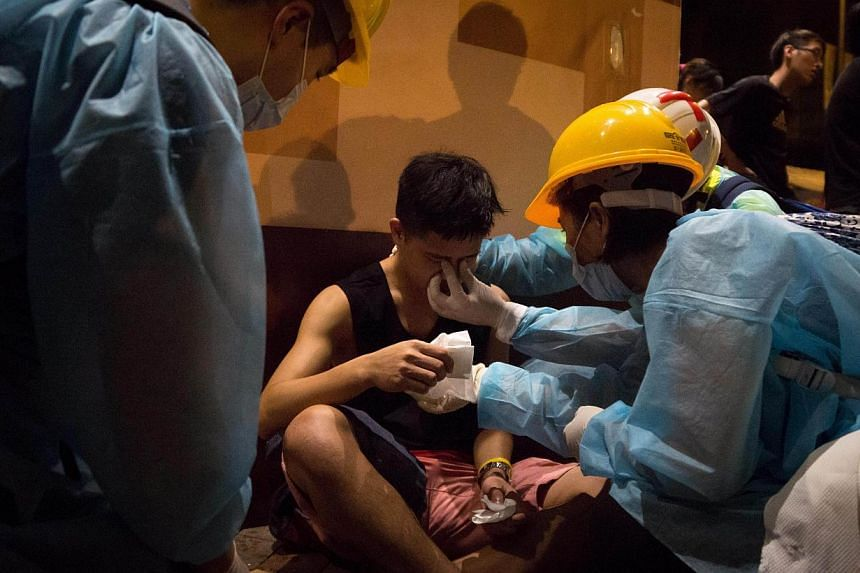 A pro-democracy protester is treated by medical volunteers after he was pepper sprayed by police in Mongkok on Oct 5, 2014. -- PHOTO: AFP
