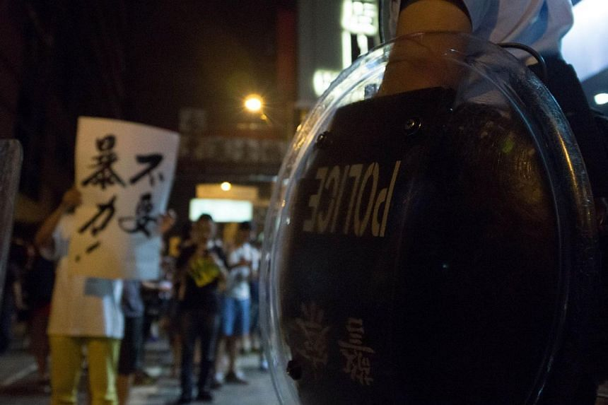 "A police officer with a riot shield stands guards as a pro-democracy demonstrator waves a sign that reads ""Violence is not necessary"" in Mongkok on Oct 5, 2014. -- PHOTO: AFP"