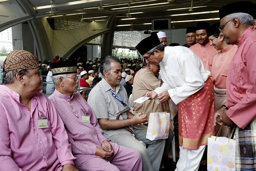 Minister-in-charge of Muslim Affairs Yaacob Ibrahim (in white), together with Muis president Mohd Alami Musa (second from right) and chairman of Assyafaah Mosque Mohd Salleh K Moideen (right) distributing meat to (from left) Mr Mohd Isa, Mr Jamaludin