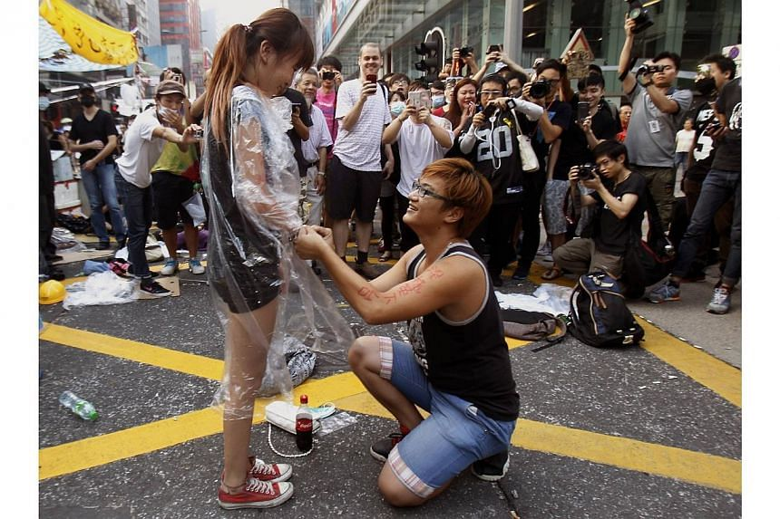 Yau Chi-hang, 22, a university student and pro-democracy protester, got on his knees and proposed to his sweetheart and fellow protester Crystal Chan, 21, at Mongkok shopping district in Hong Kong on Oct 5, 2014. Her answer, a resounding yes, drew ch