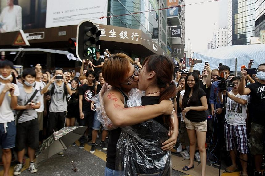Yau Chi-hang, 22, a university student and pro-democracy protester, kisses fellow protester Crystal Chan, 21, after she agreed to his marriage proposal, at Mongkok shopping district in Hong Kong on Oct 5, 2014, to the cheers of the crowd. -- PHOTO: R