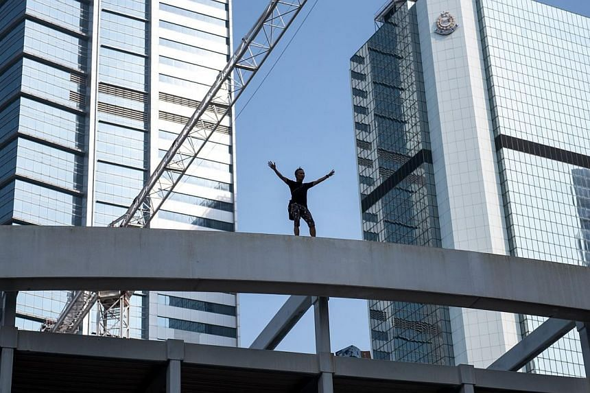 A man standing on top of a bridge overlooking a pro-democracy protest area shouts at onlookers and threatens to jump, near the central government offices in Hong Kong on Oct 5, 2014. The man, who claimed to be a father of three, complained with a meg