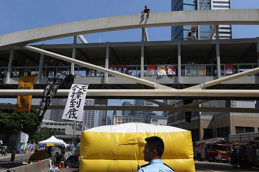 Firefighters put up a huge inflatable cushion under the bridge in case he fell, Radio Television Hong Kong reported.-- PHOTO: AFP